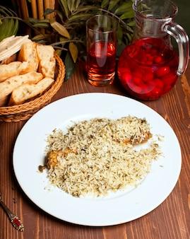 Arroz plov de pollo con hierbas en plato blanco y composto