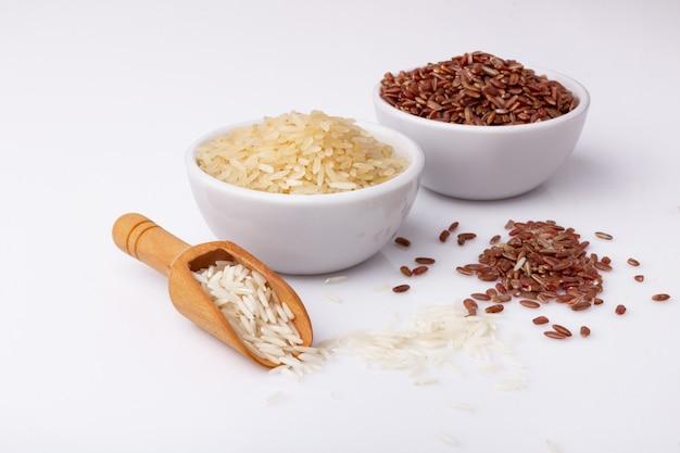 Arroz rojo y blanco con cuencos y cuchara de madera en blanco