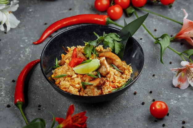 Arroz tailandés con pollo. plato tailandés de arroz, pollo, cebolla yalta, maíz, piña, tomate, salsa de soja, pasta de chile, cilantro, lima, ají