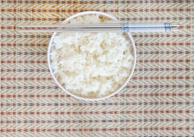 Arroz en un tazón blanco con palillos