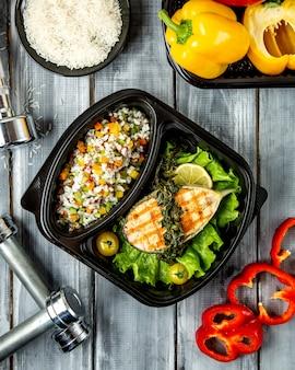 Arroz con verduras y rodajas de pescado.