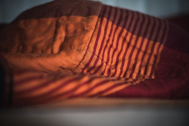 Arruga la manta desordenada en el dormitorio después de levantarte por la mañana