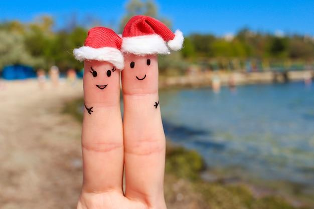 Arte del dedo de una pareja feliz descansando en el mar. pareja abrazándose en los sombreros de año nuevo.