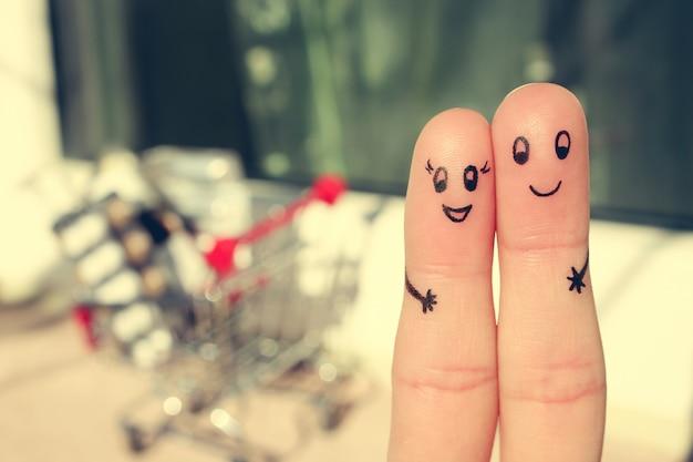 Arte del dedo de una pareja feliz. un hombre y una mujer abrazan con carrito de compras. imagen tonificada