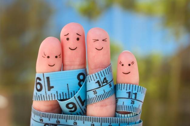 El arte de los dedos de una familia feliz con cinta métrica. concepto de perder peso juntos.