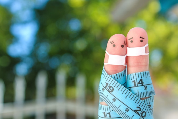 Arte de los dedos de la feliz pareja con cinta métrica. concepto de deportistas en máscara médica de covid-2019.