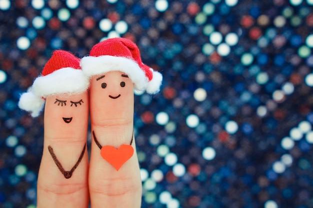 El arte de los dedos de la pareja celebra la navidad con sombreros de año nuevo.