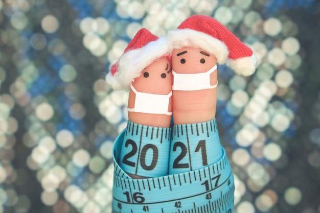 El arte de los dedos de la pareja en la máscara médica de covid-2019 celebra la navidad.
