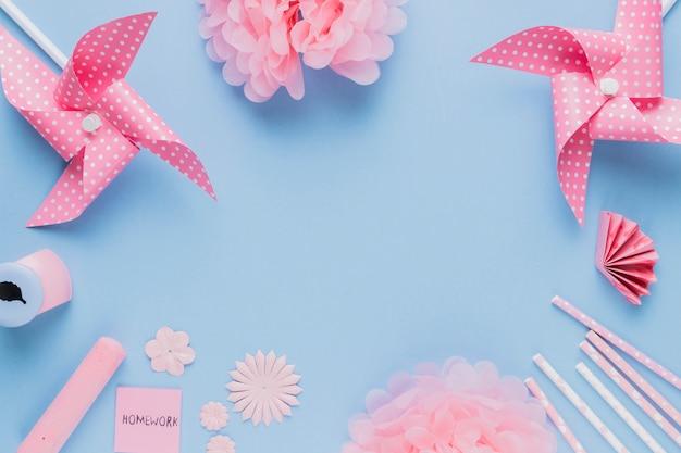 Arte y equipo rosados del arte del origami dispuestos en marco circular en fondo azul