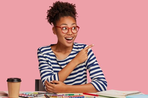 Arte estacionario. alegre mujer de etnia negra con expresión alegre, usa anteojos para una buena visión, señala en la esquina superior derecha, nota algo asombroso, usa cuaderno, lápices de colores para dibujar