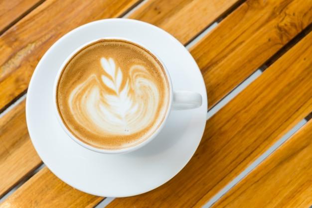 Arte del latte café en la mesa de madera