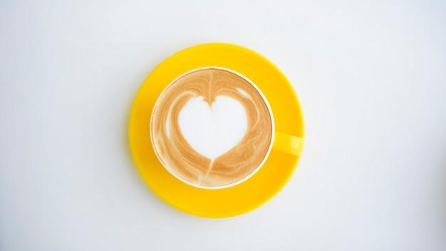 Arte latte caliente en taza amarilla en el escritorio de trabajo