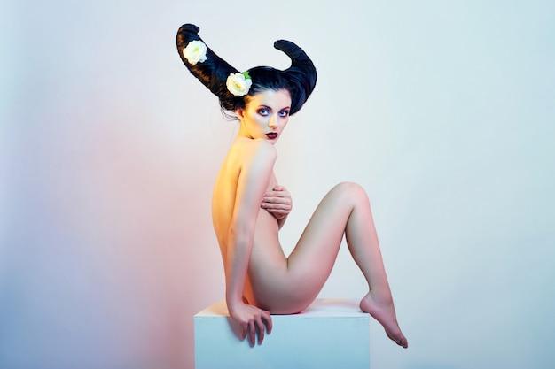 Arte moda mujer desnuda con cuernos de pelo sentado en un cubo blanco. hermosa mujer morena diablo, mujer demonio cachonda. cuerpo perfecto y maquillaje brillante.