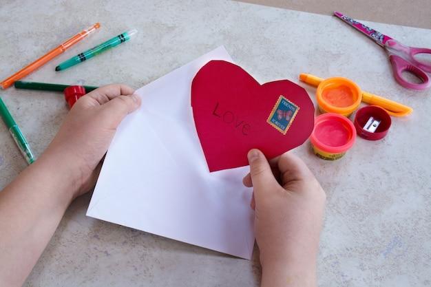 Arte para niños, tema del día de san valentín. concepto de artesanía. niño poniendo corazón rojo en un sobre.