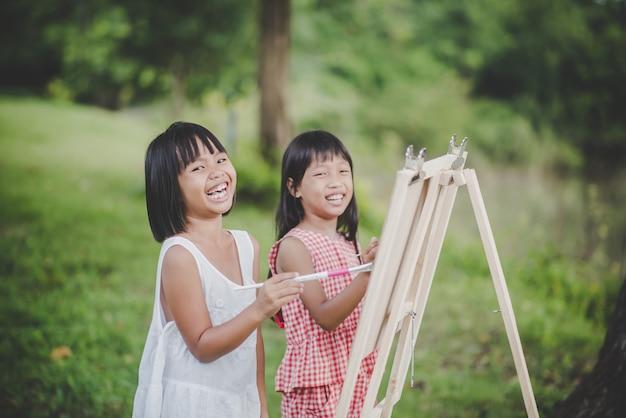 Arte del pintor de dos pequeñas muchachas que dibuja en el parque