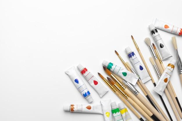 Arte de la pintura. conjunto de pintura: pinceles, pinturas, pintura acrílica sobre fondo blanco.