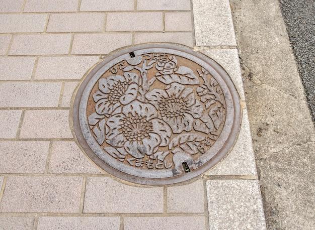 El arte sobre el tapón de drenaje en la calle en la prefectura de fukuoka