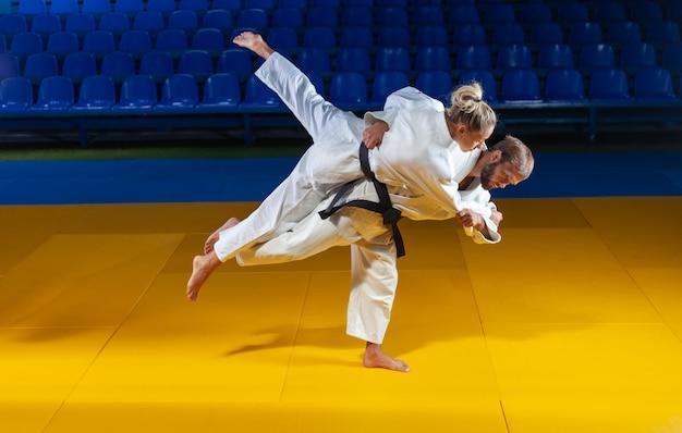 Artes marciales. ahorradores de porteros. deporte hombre y mujer en kimono blanco entrena judo lanza y captura en el pabellón deportivo