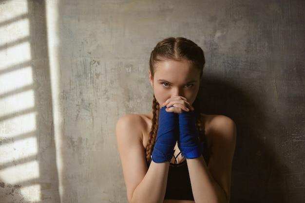 Artes marciales, lucha, boxeo y kickboxing. close up retrato de autodeterminada chica deportiva confiada estrechando las manos envueltas en vendajes, listo para la pelea