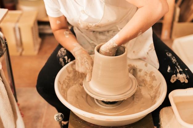 Artesana alfarera en delantal trabajando en rueda