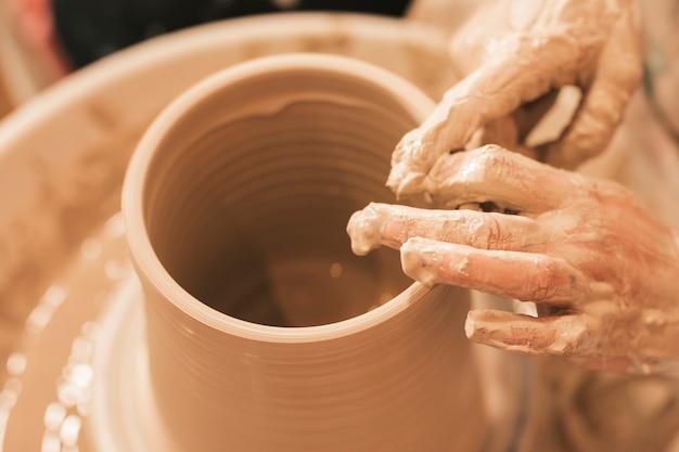 La artesana da forma a la olla de barro con las manos en la rueda de alfarería.