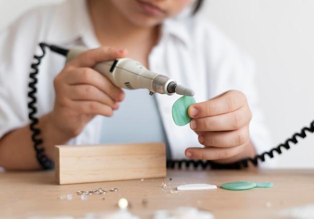 Artesana trabajando en el atelier con pistola de pegamento