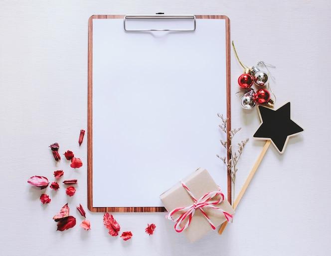 Artesanía y cuaderno mock up portapapeles con adornos de navidad sobre fondo blanco de madera