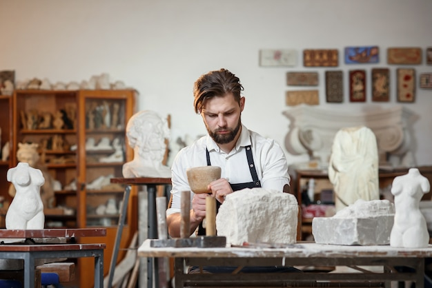Artesano barbudo trabaja en talla de piedra blanca con un cincel. taller creativo con obras de arte.