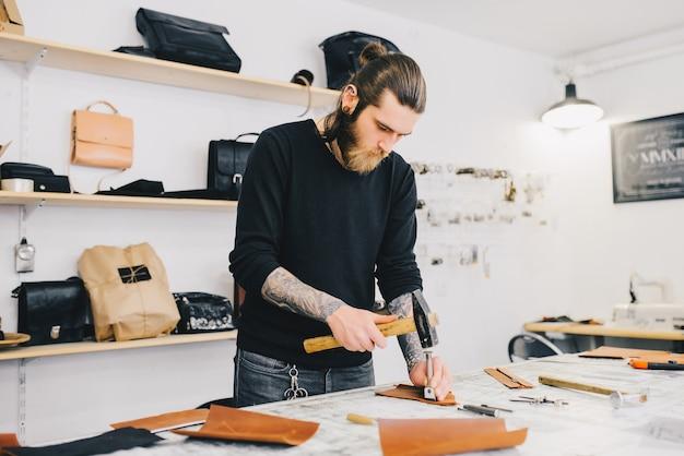 Artesano de cuero que trabaja con cuero usando el martillo.