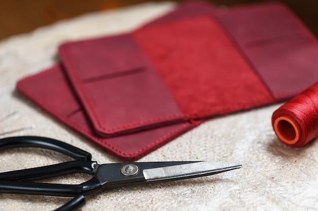 Un artesano de cuero trabaja con cuero. cose artículos de cuero. hacer cosas a mano.