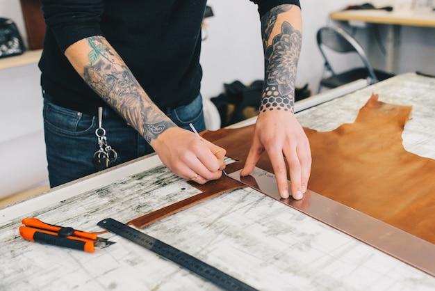 Artesano de cuero trabajando haciendo measupenets en patrones en la mesa en taller de estudio