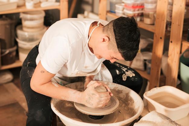 Artesano haciendo jarrón de arcilla fresca húmeda en la rueda de alfarería