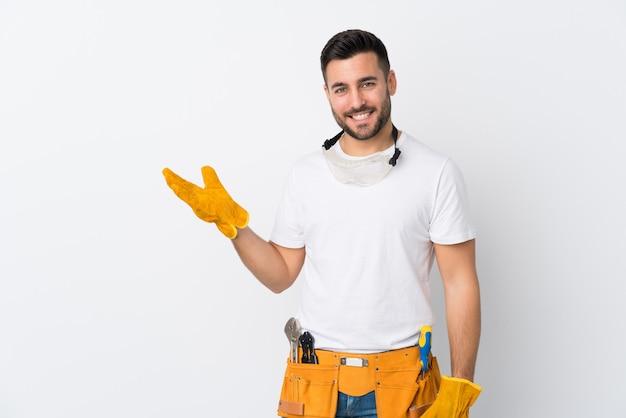 Artesanos o electricista hombre sobre pared blanca aislada con copyspace imaginario en la palma