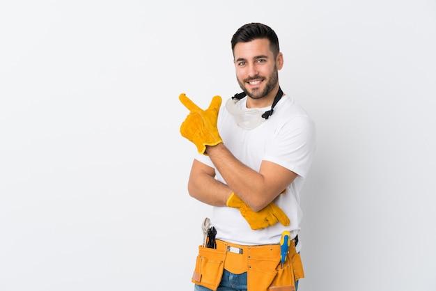Artesanos u electricista hombre sobre pared blanca aislada apuntando el dedo hacia un lado