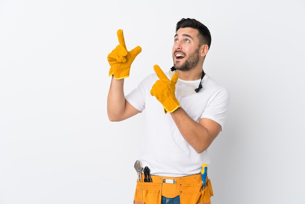 Artesanos u hombre electricista sobre pared blanca aislada señalando con el dedo índice una gran idea