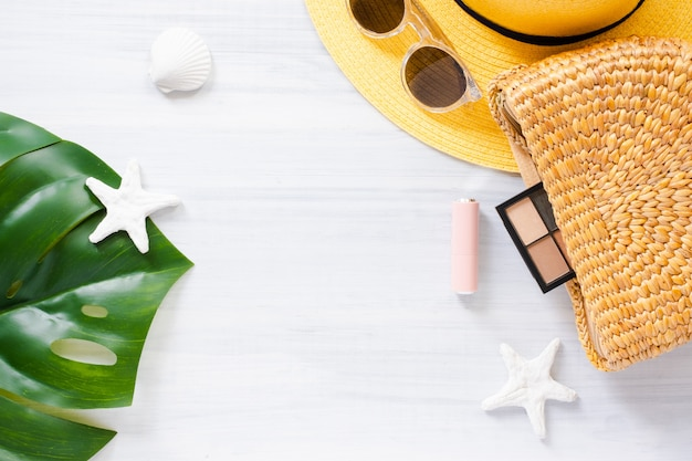 Artículo de verano en mesa de madera blanca. bolso de mimbre y hoja de monstera con cosmética.