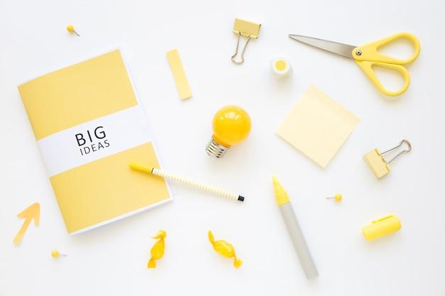 Artículos de papelería, bombilla y dulces con diario de grandes ideas