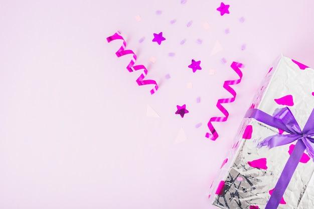 Artículos decorados con caja de regalo envuelta con cinta morada sobre fondo rosa