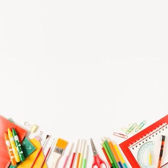 Artículos escolares sobre fondo blanco plano lay