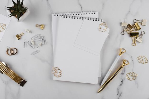 Artículos de escritorio planos sobre mesa de mármol