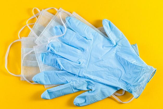 Artículos de higiene que consisten en guantes de látex y máscara sobre fondo amarillo.
