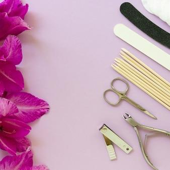 Artículos de manicura y pedicura con flores de gladiolo sobre una mesa lila.