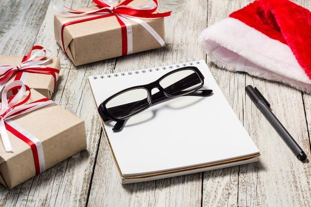 Artículos navideños y comerciales con santa cap bloc de notas, vasos, bolígrafos y cajas de regalo decoradas.