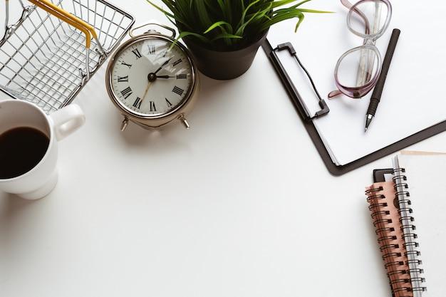 Artículos de negocios caídos en desorden creativo en mesa blanca