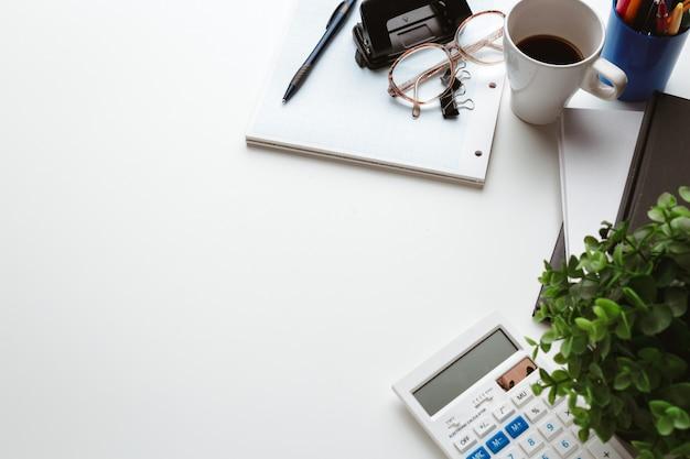 Artículos de negocios cayeron en el desorden creativo en la mesa blanca