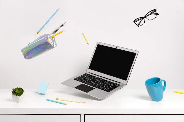 Artículos de oficina papelería levitar sobre mesa blanca