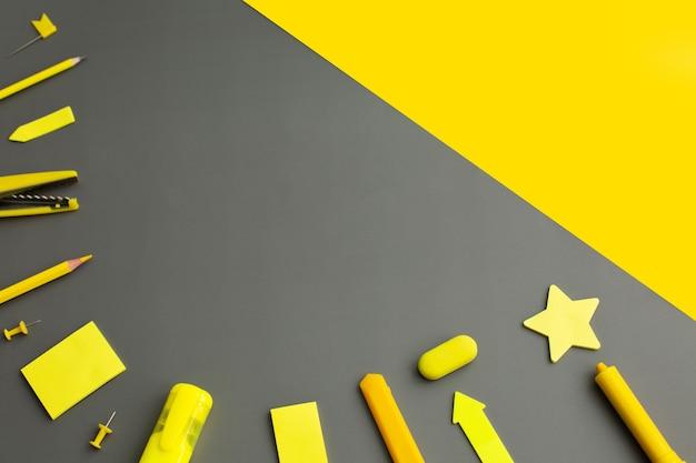 Artículos de papelería amarillo accesorios de herramientas de escritura bolígrafos lápices sobre fondo gris. de vuelta a la escuela. productos de suministros de oficina