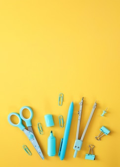 Artículos de papelería azul sobre fondo amarillo con espacio libre para texto. fondo creativo y colorido con útiles escolares. flatlay con espacio de copia, vista superior. rotulador, bolígrafo, sujetapapeles, tijeras.