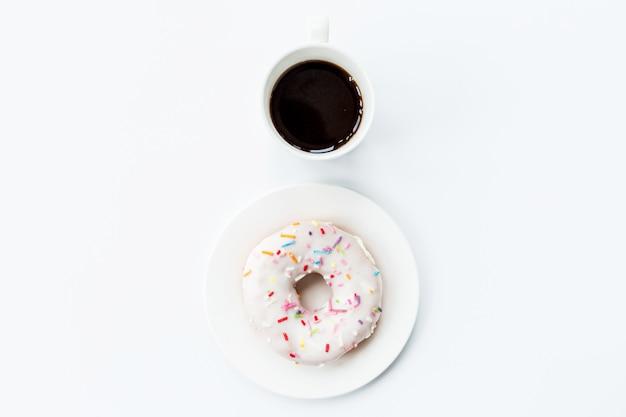 Artículos planos: taza de café y donut acostado sobre fondo blanco.
