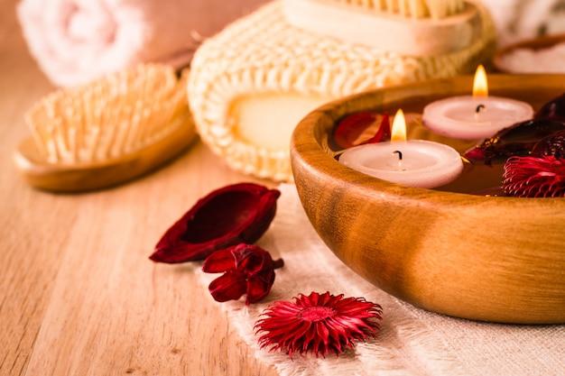 Artículos para tratamientos de spa. velas y flores secas fragantes en agua, sal marina, cepillo, toallas y cepillo para el pelo en una mesa de madera